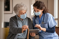 nurse talking to elderly patient at home with masks on